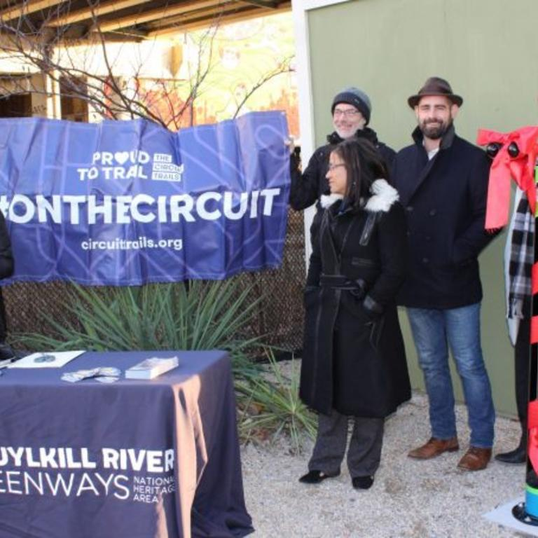 Holding banner on right, HBK's David Landrecht attends ribbon cutting for new fix-it stations on Schuykill River Trail